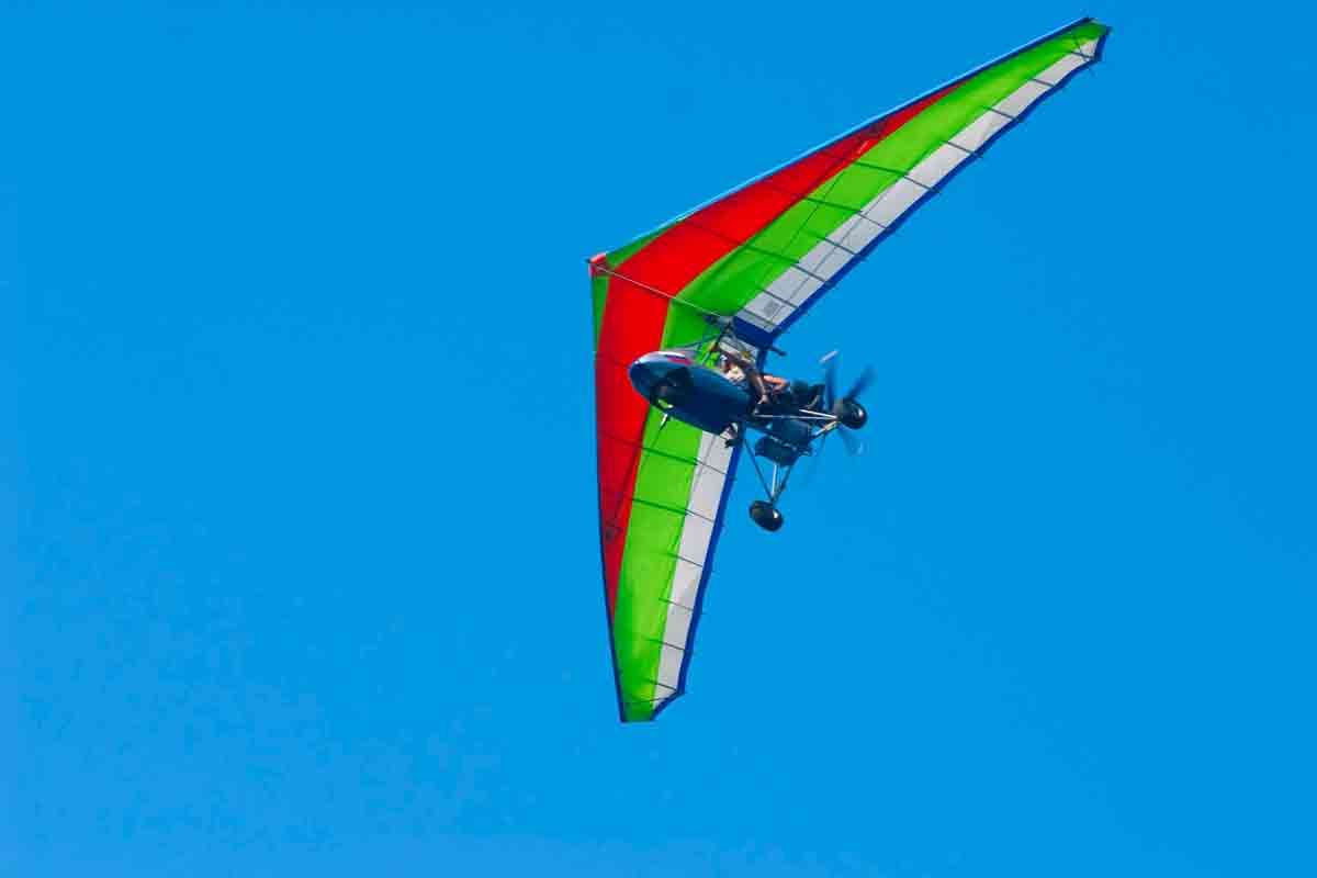 Ultralight Aircraft - soaring a motorized hang-glider on a background blue sky